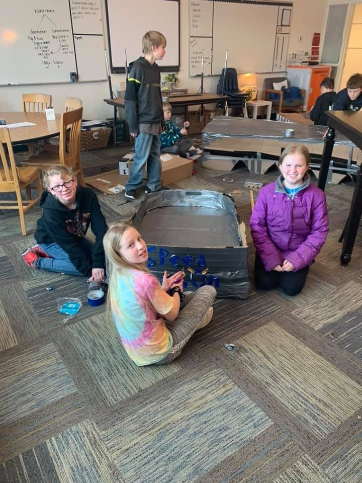 kids building their box sled in classroom