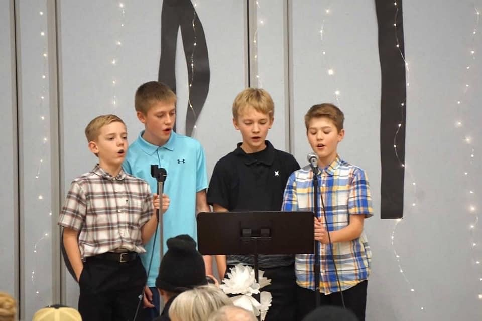 4 boys singing on stage